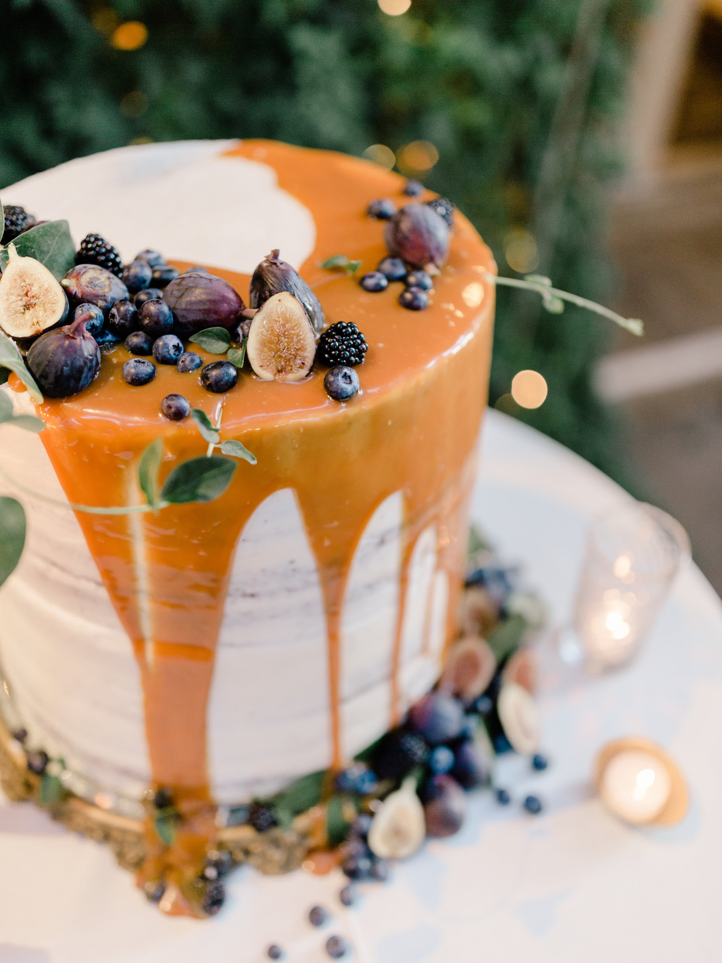 Autumn semi naked wedding cake overflowing with caramel, fruit, berries, figs and vines with an old world charm for fall | Decorated by Finding Flora