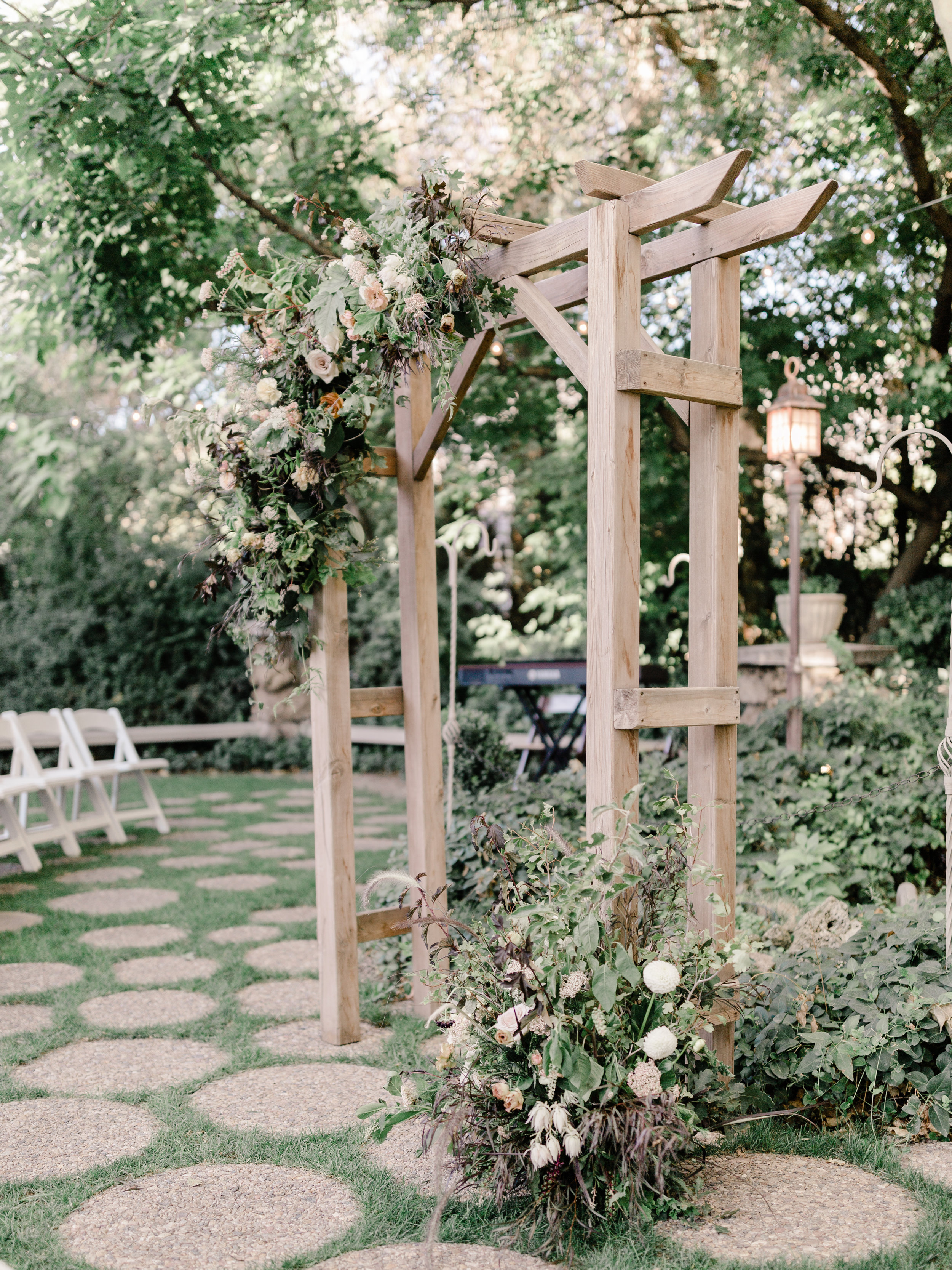 A natural wooden arch with burgundy for an early autumn wedding at The Bungalow in Pleasant Grove, Utah