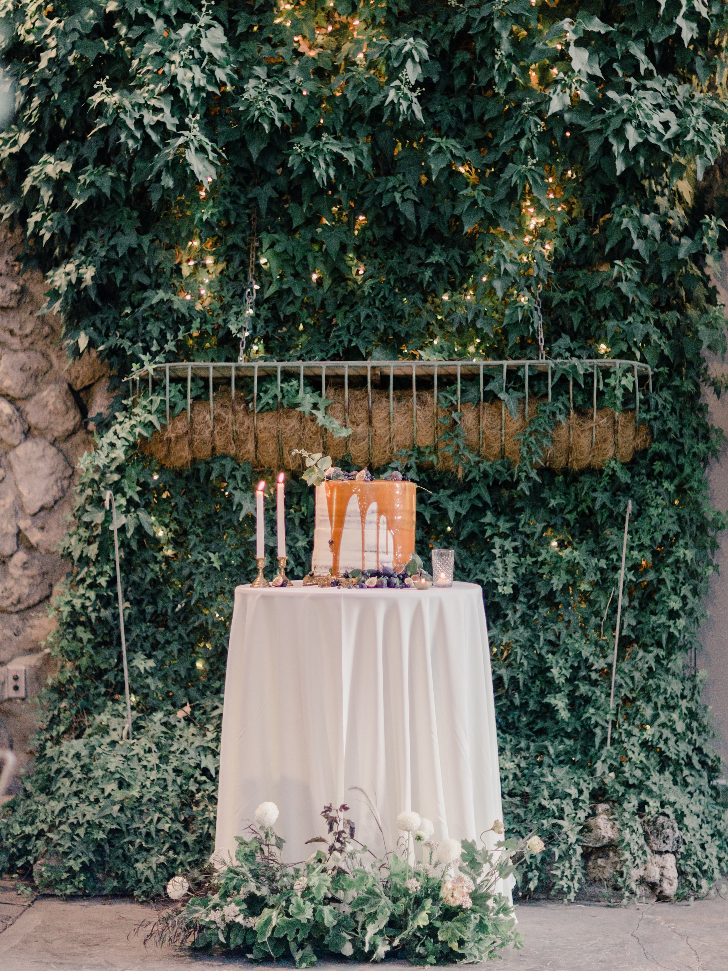 The dreamiest caramel covered semi naked wedding cake at this overgrown garden venue covered in figs, berries, fruit and vines for this early Autumn wedding
