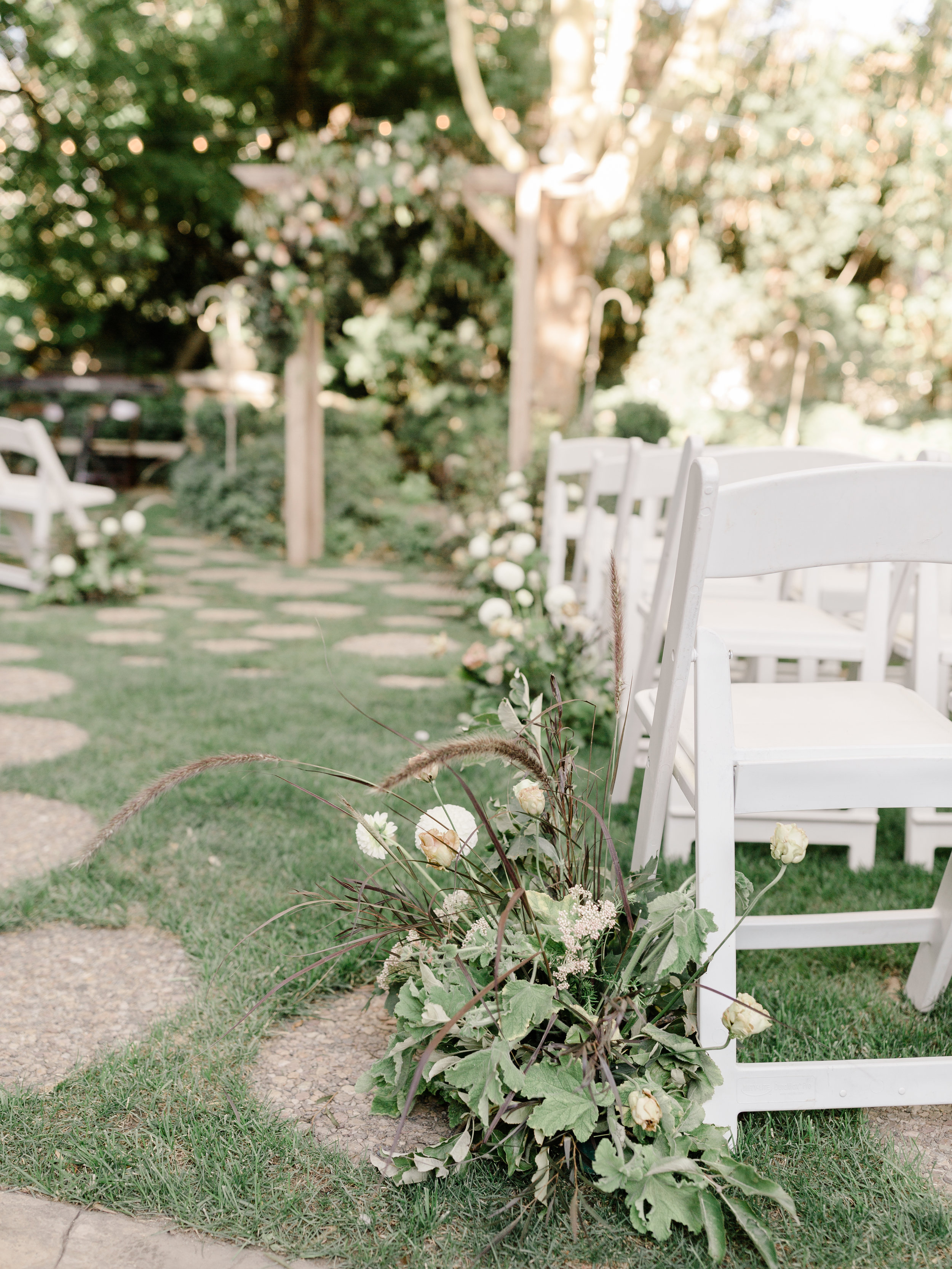 Ceremony aisle markers full of grasses and blooms for this organic garden wedding at The Bungalow in Utah