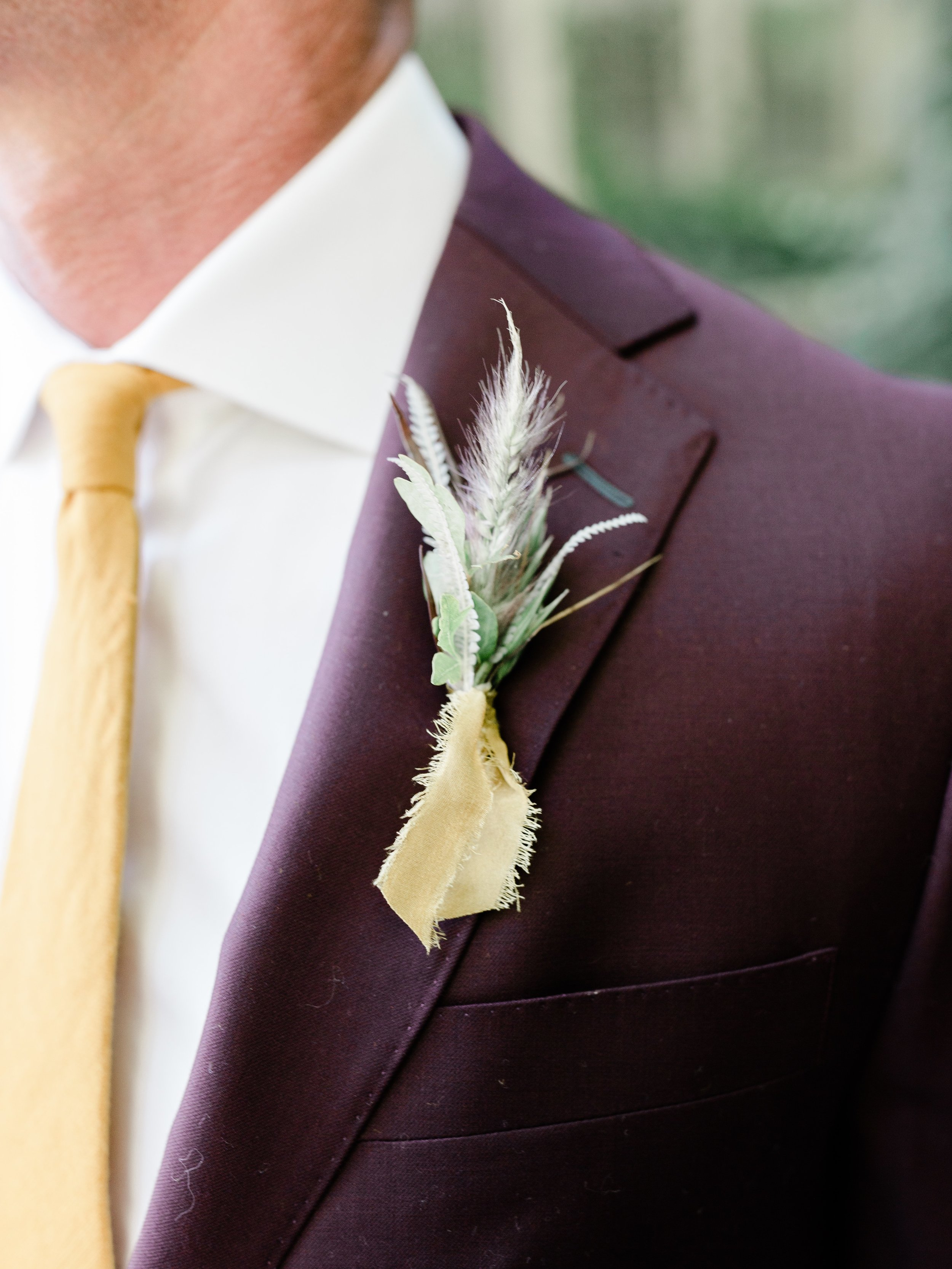 Organic boutonniere tied with golden ribbon