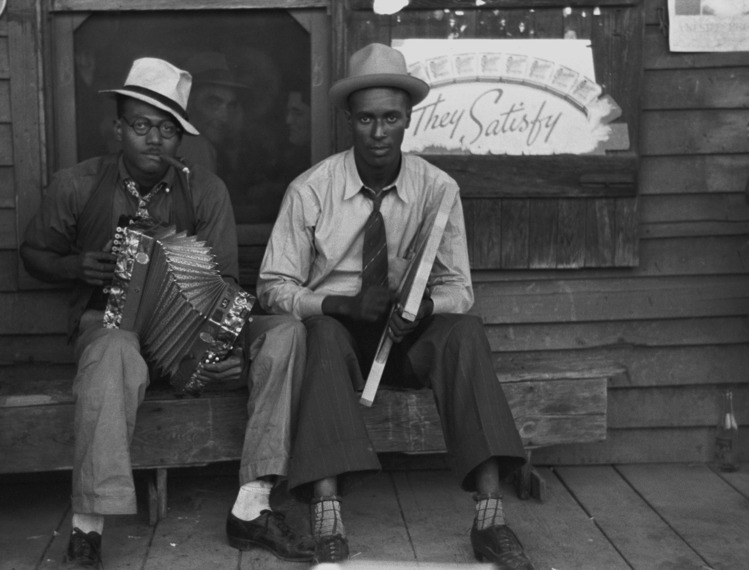 "Early Creole musicians playing an accordion and a washboard in front of a store, near Opelousas, Louisiana (1938). Zydeco music originated from Creole music — today's rubboard or frottoir (""rubbing the washboard"") is a stylized version of the early washboard. Image courtesy of Russell Lee / United States Library of Congress's Prints and Photographs division"