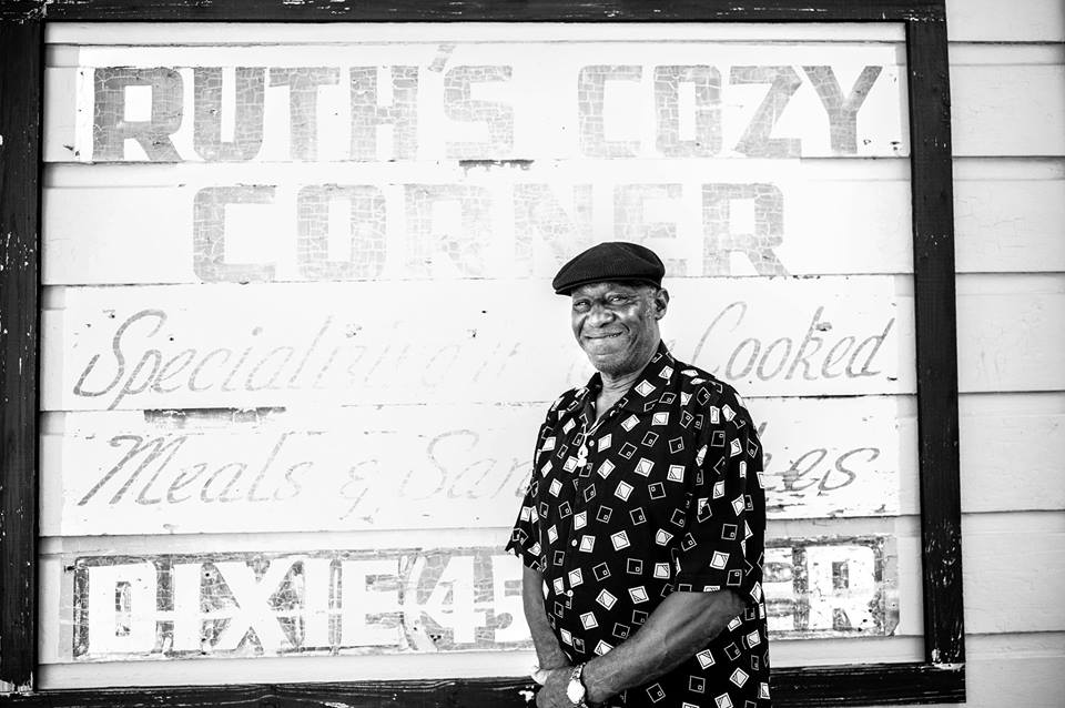Benny Jones, Sr. in front of Ruth's Cozy Corner on Ursulines and North Robertson in Tremé, where his stepmother ran a club that was home to many brass bands. The bar continued to host parades when Joseph Glasper, Sr. took over the bar and renamed it Joe's Cozy Corner. Photograph by Bruce Sunpie Barnes.