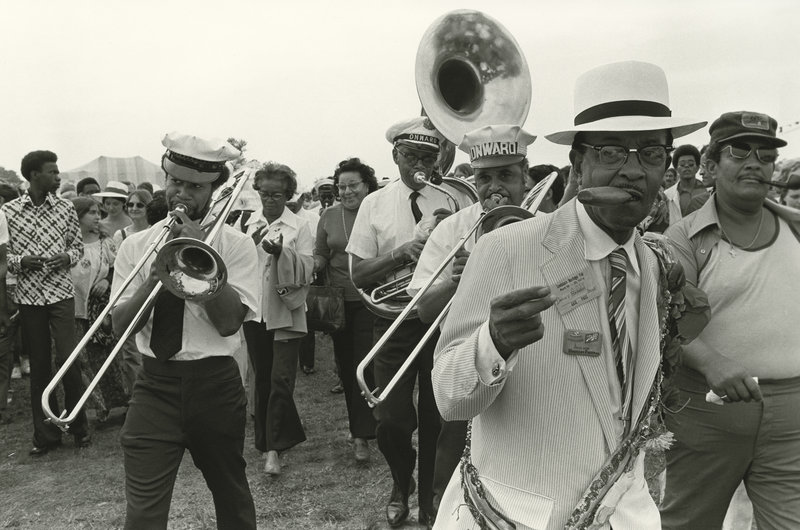 Sporting a plastic cigar in his mouth, Danny Barker leads the Onward Brass Band in a parade at the 1974 New Orleans Jazz and Heritage Festival. Michael P. Smith/The Historic New Orleans Collection