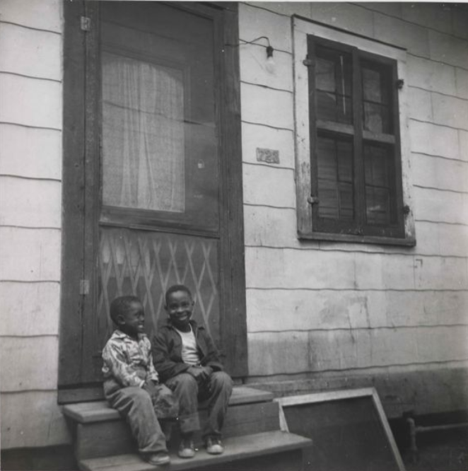 Two boys sitting on the front porch of Louis Armstrong's childhood home.