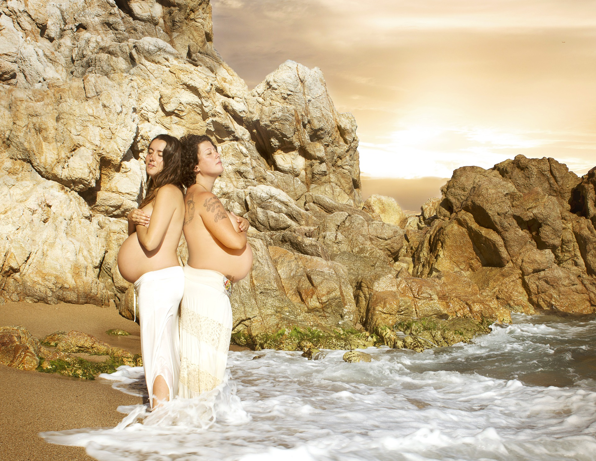 Two pregnant women wearing white pants and standing back to back in water with rocks in the background [Rising Tide Women's Whole Life Wellness]