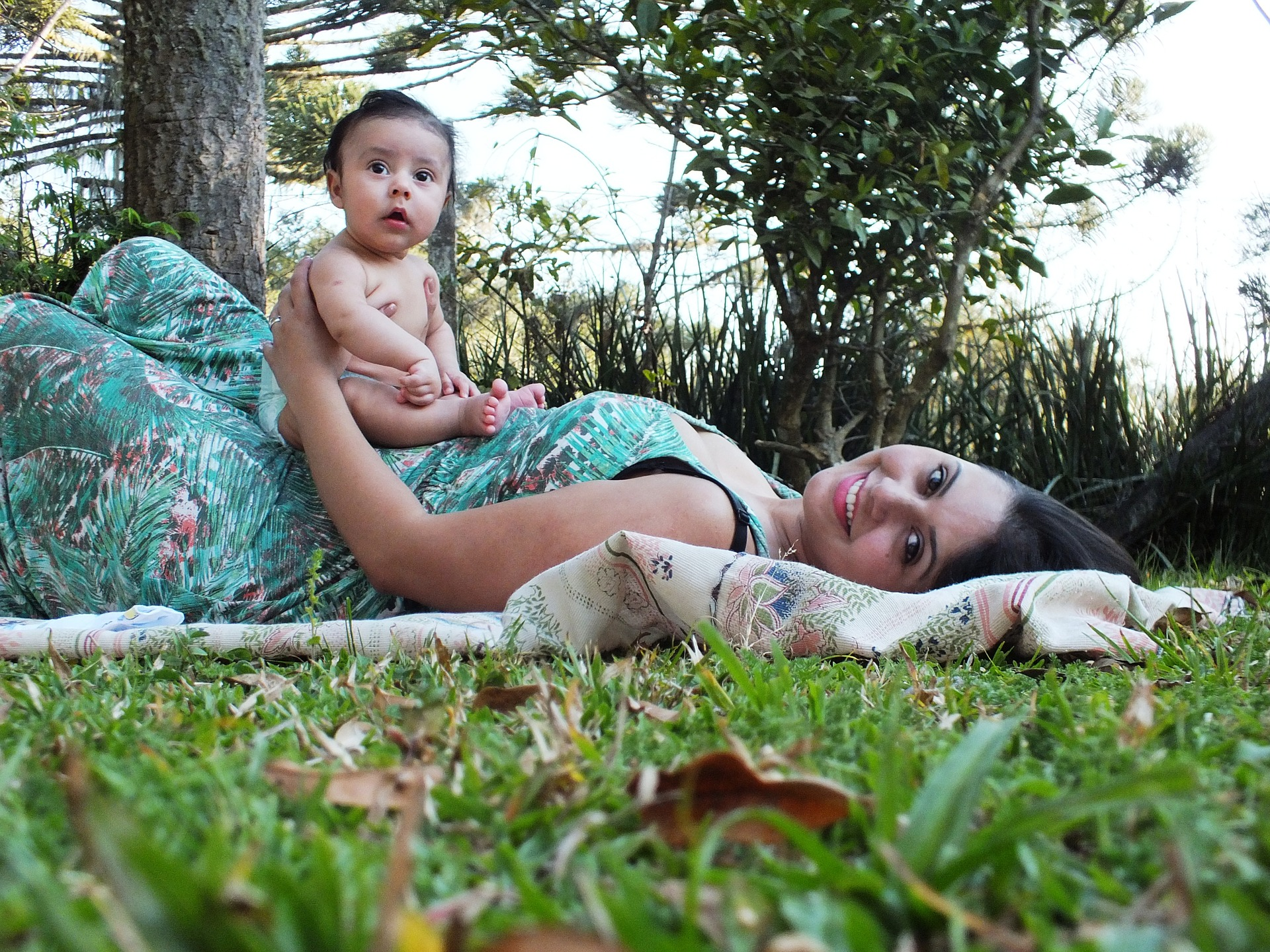 Mom laying on the grass with baby balanced on her belly, smiling at the camera [Rising Tide Women's Whole Life Wellness]
