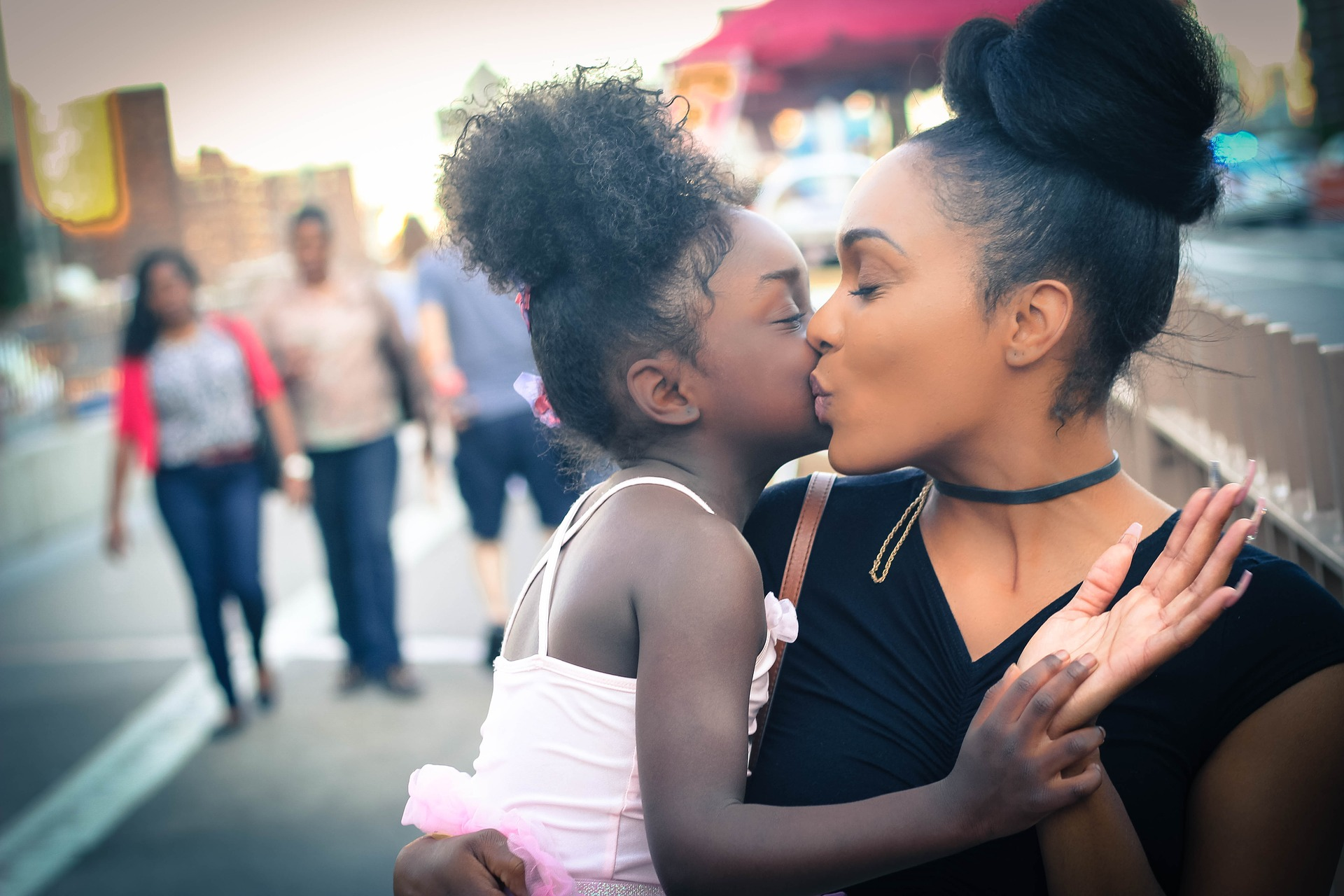 Mom kissing little girl with natural Black hair [Rising Tide Women's Whole Life Wellness]