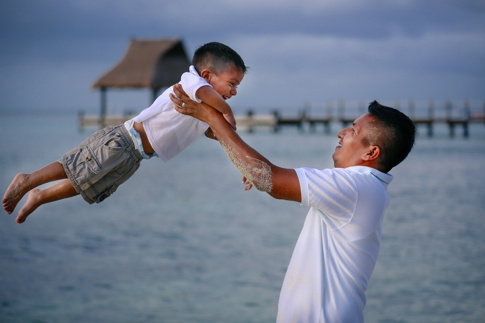 Father swinging little boy in the air. Both are smiling and the ocean is in the background. [Rising Tide Women's Whole Life Wellness]