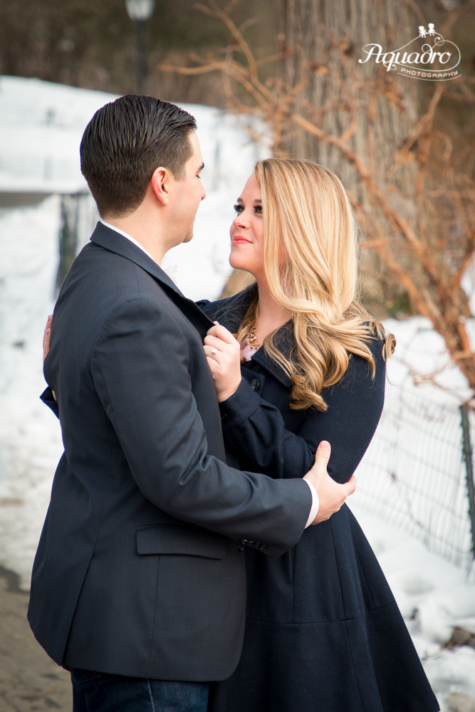 engaged couple embrace in snowy Central Park