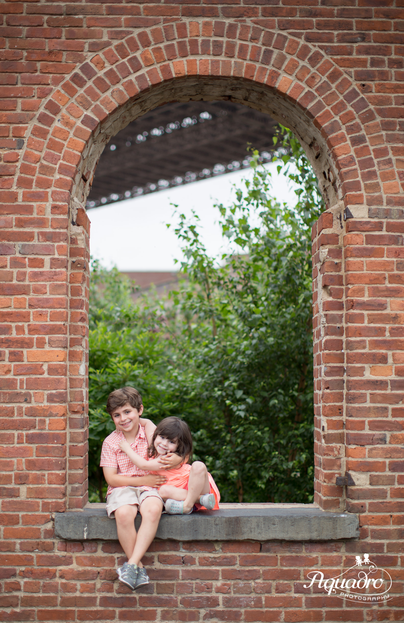 Brother and sister hug each other in the brick archway of St. Ann's Warehouse during a rainy family photo mini session in Brooklyln Bridge Park