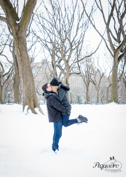 engaged couple embrace and kiss in snowy Central Park