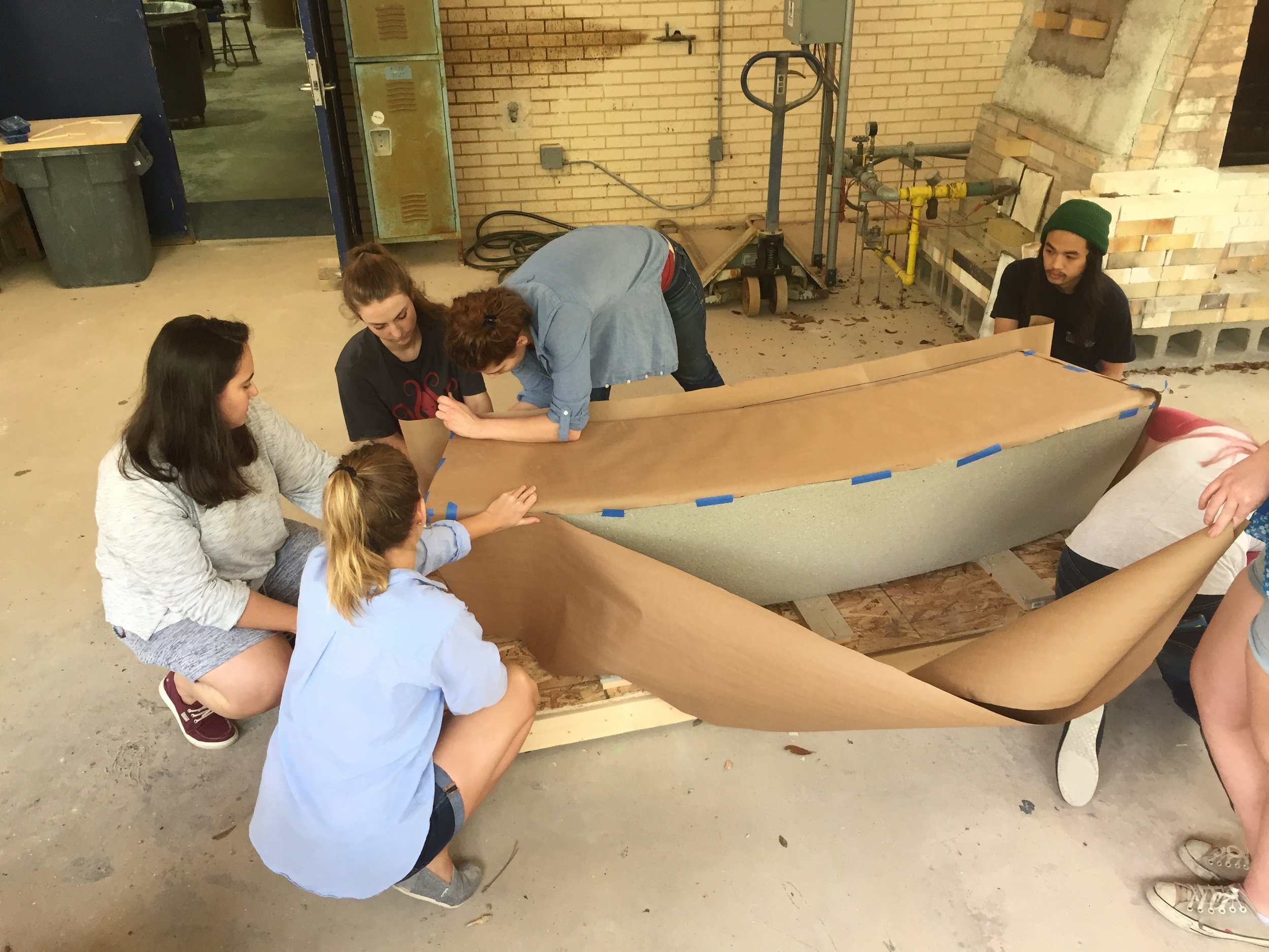 Students using butcher paper to create a template of the concrete bench.