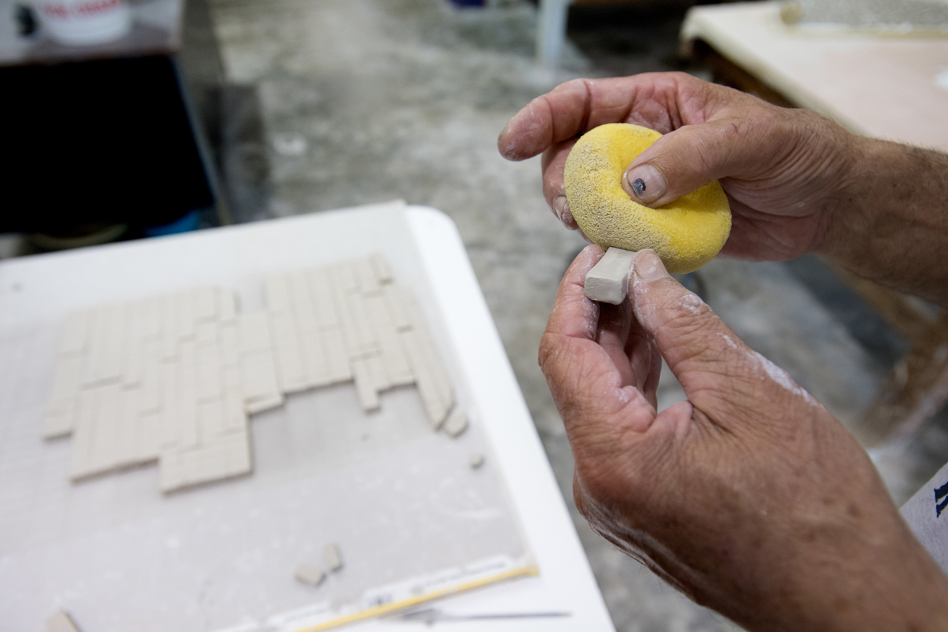 Unfired tiles being sponged prior to firing to soften and round the edges.  Photo by Michael Spooneybarger