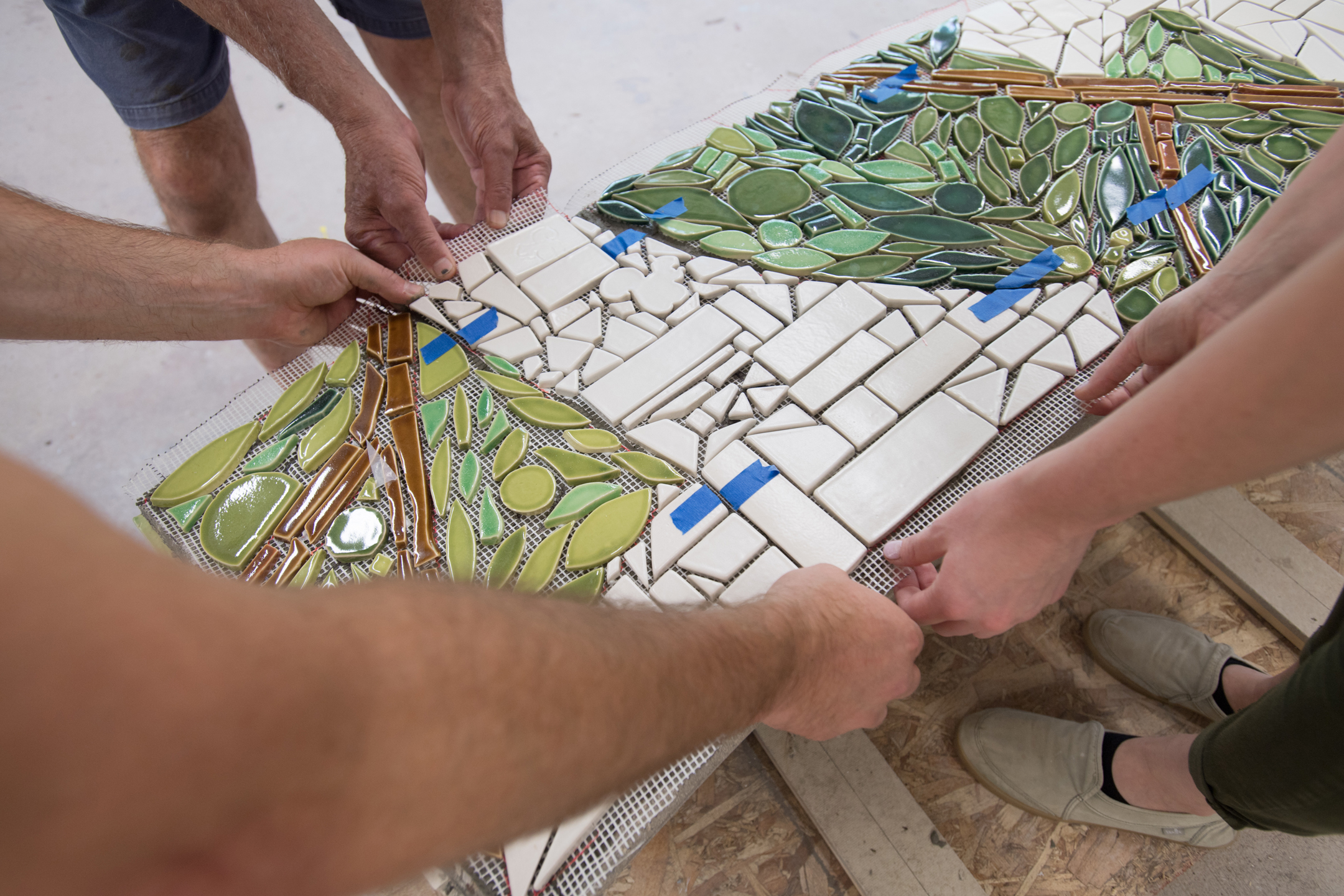 Because the mosaic had to be cut into sections so that it could be lifted and placed on the bench, blue painters' tape was used as registration marks so that each piece could be aligned correctly.  Photo by Michael Spooneybarger
