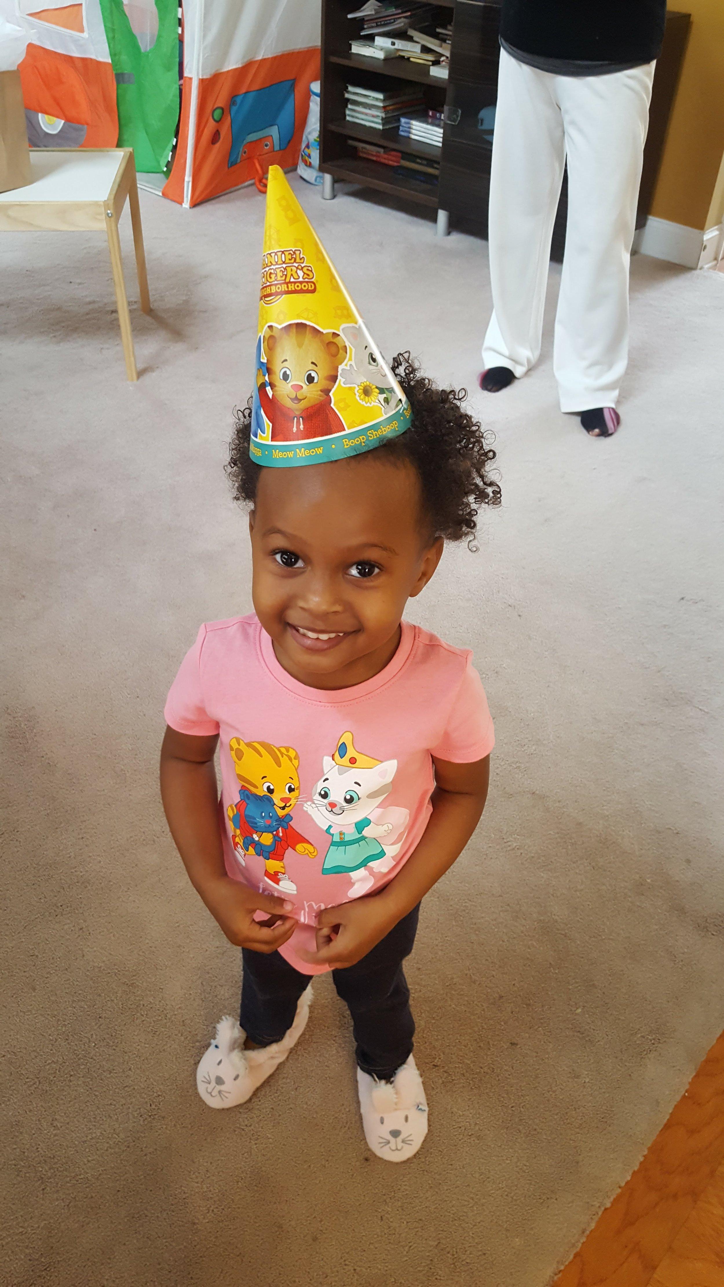 Big sister sporting birthday hat
