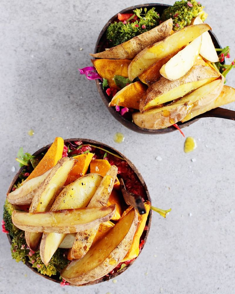 Salad bowls with Salty Baked Vegetables on top, oil drizzled afterwards.