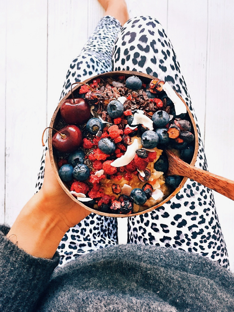 Superfood porridge topped with freeze dried berries, fresh cherries, blueberries, cacao nibs and chia seeds.