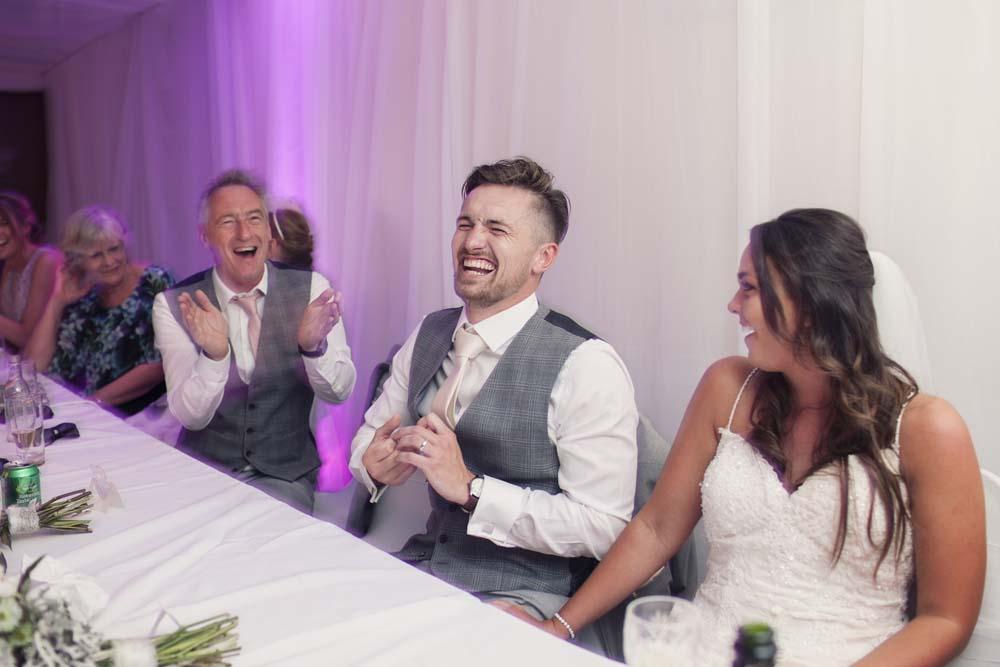 Groom having fun during the speeches at his wedding Preston Lancashire