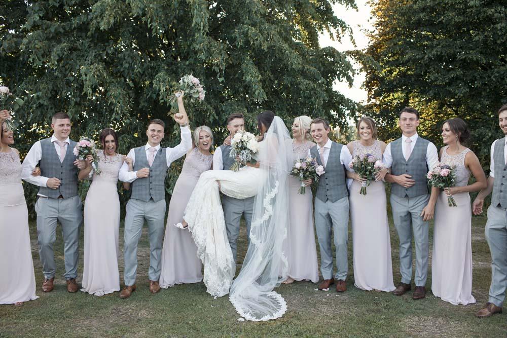 Bridesmaids and groomsmen celebrating the bride and groom having fun DIY wedding Preston Lancashire
