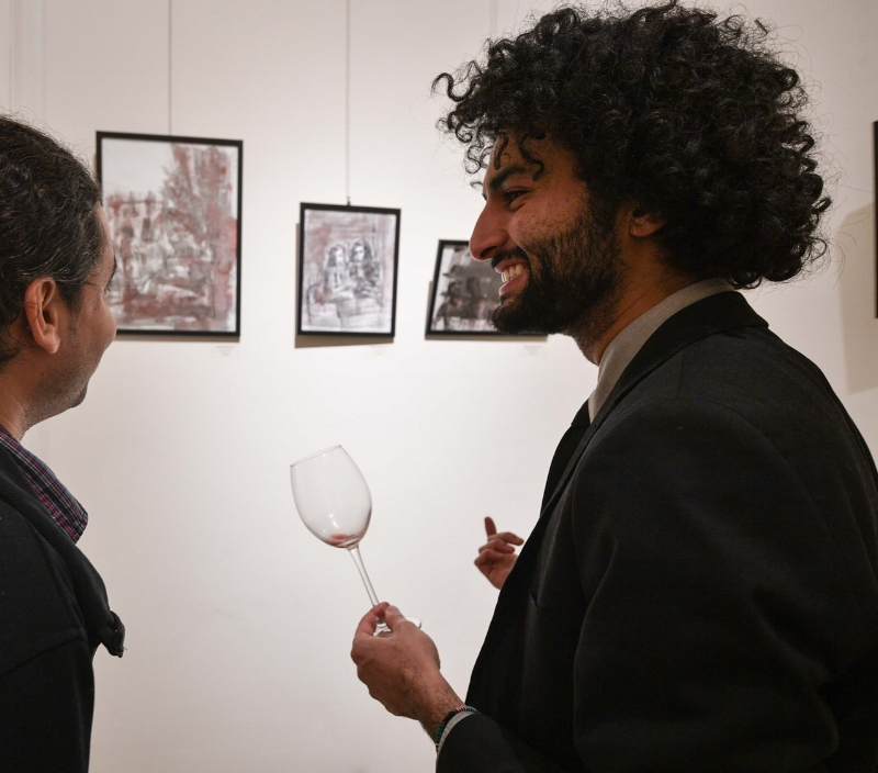 """Wissam Shaabi (on the left) talking with Christopher Ibrahim (musician) about its series ink and watercolor """"Vision trough wine"""""""