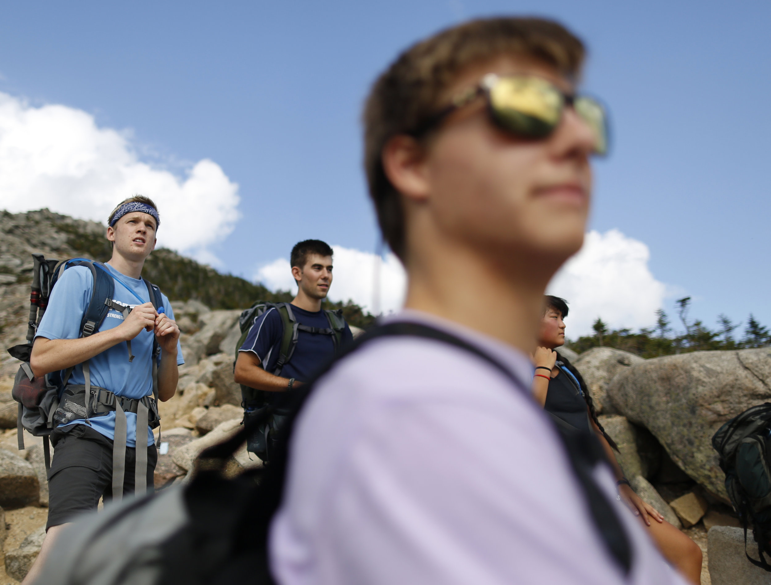 Josh Rines, Nate Moreau, Will Bolduc, and Monata Song, left to right, pause en route to the summit of South Turner Mountain to catch a glimpse of Mount Katahdin, the highest peak in Maine.