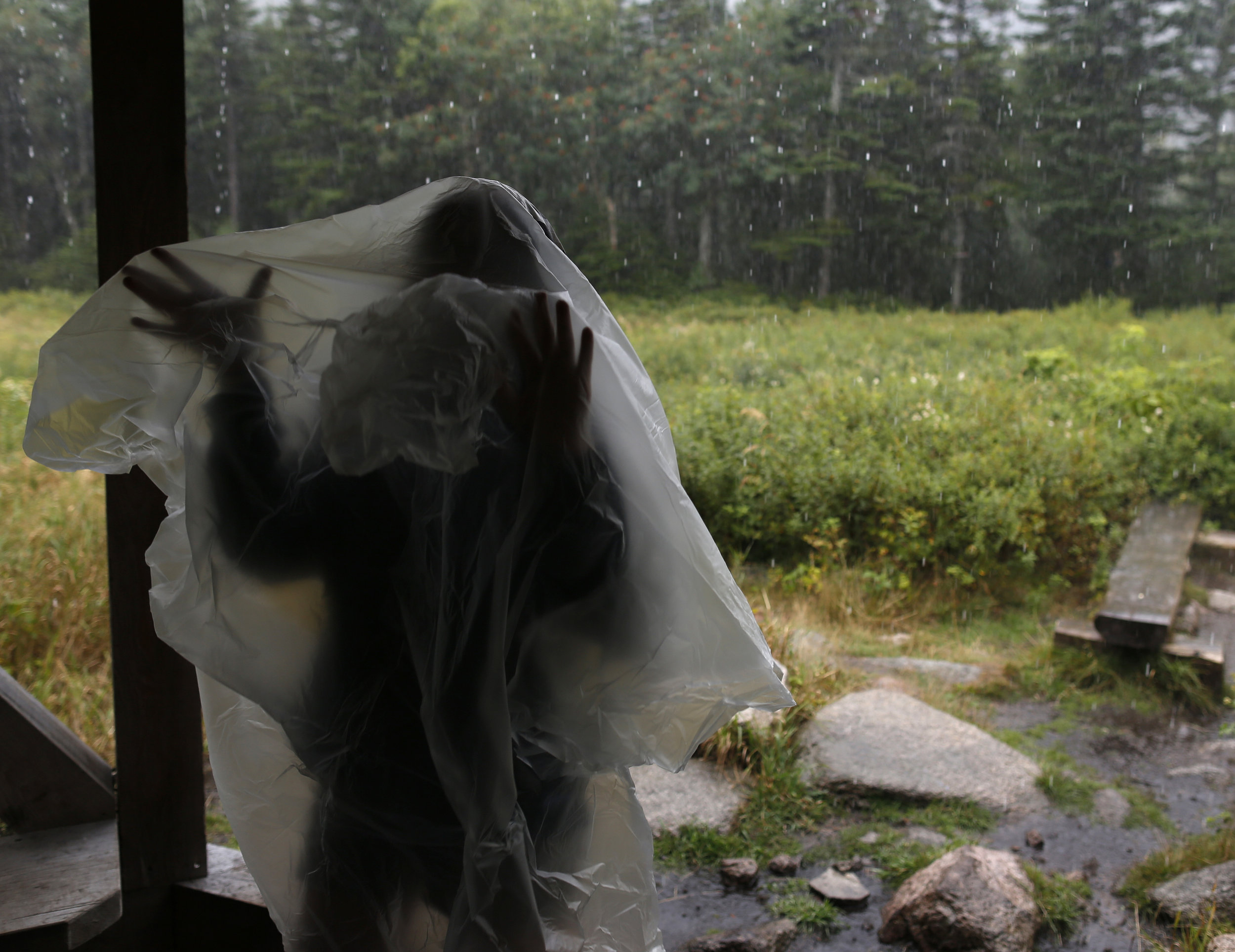 Monata dons a rain poncho at a shelter partway back to the campsite. Lankin had turned the group around near the summit to avoid getting caught in a storm above the tree line.