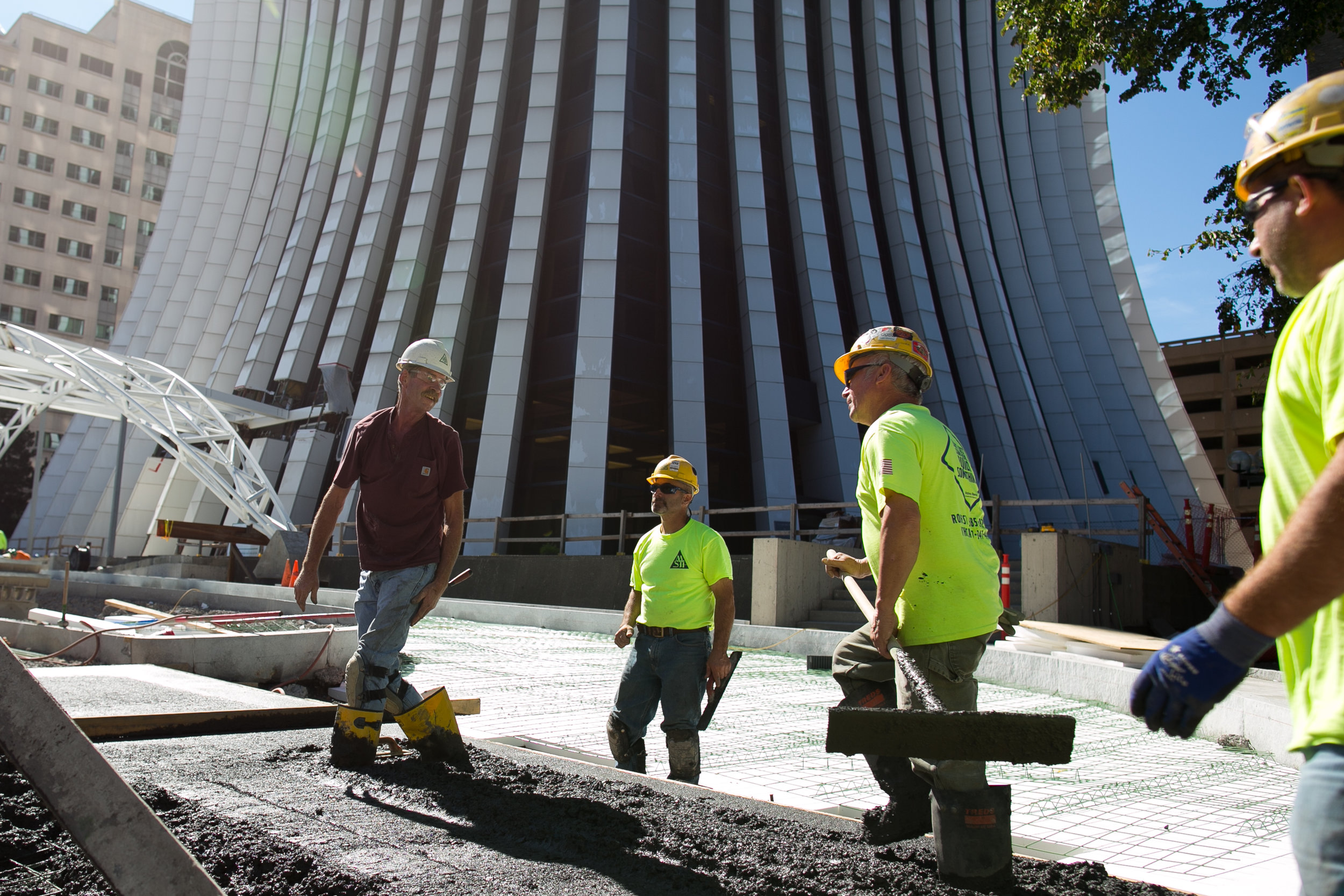 Workers pour a new driveway at The Metropolitan in Rochester, New York on Wednesday, October 5, 2016. The 26-story former Chase Tower is undergoing a $30-million renovation to modernize office space, and to add condominiums and apartments.