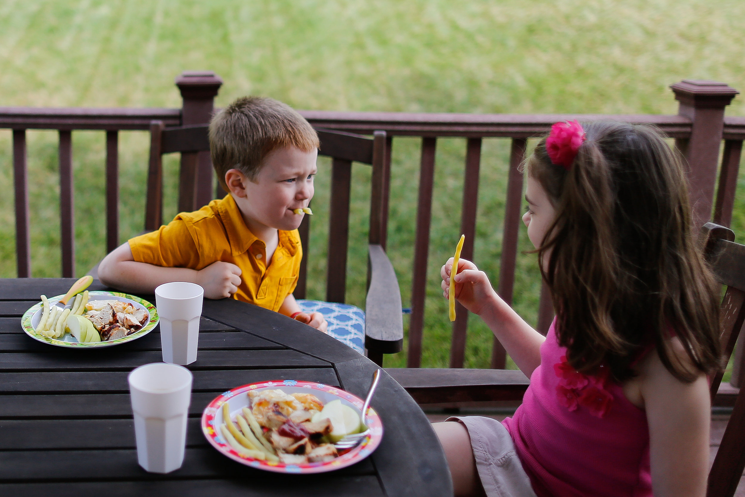 Evan Costik, 6, and his sister Sarah, 8, sit down for dinner on the patio.