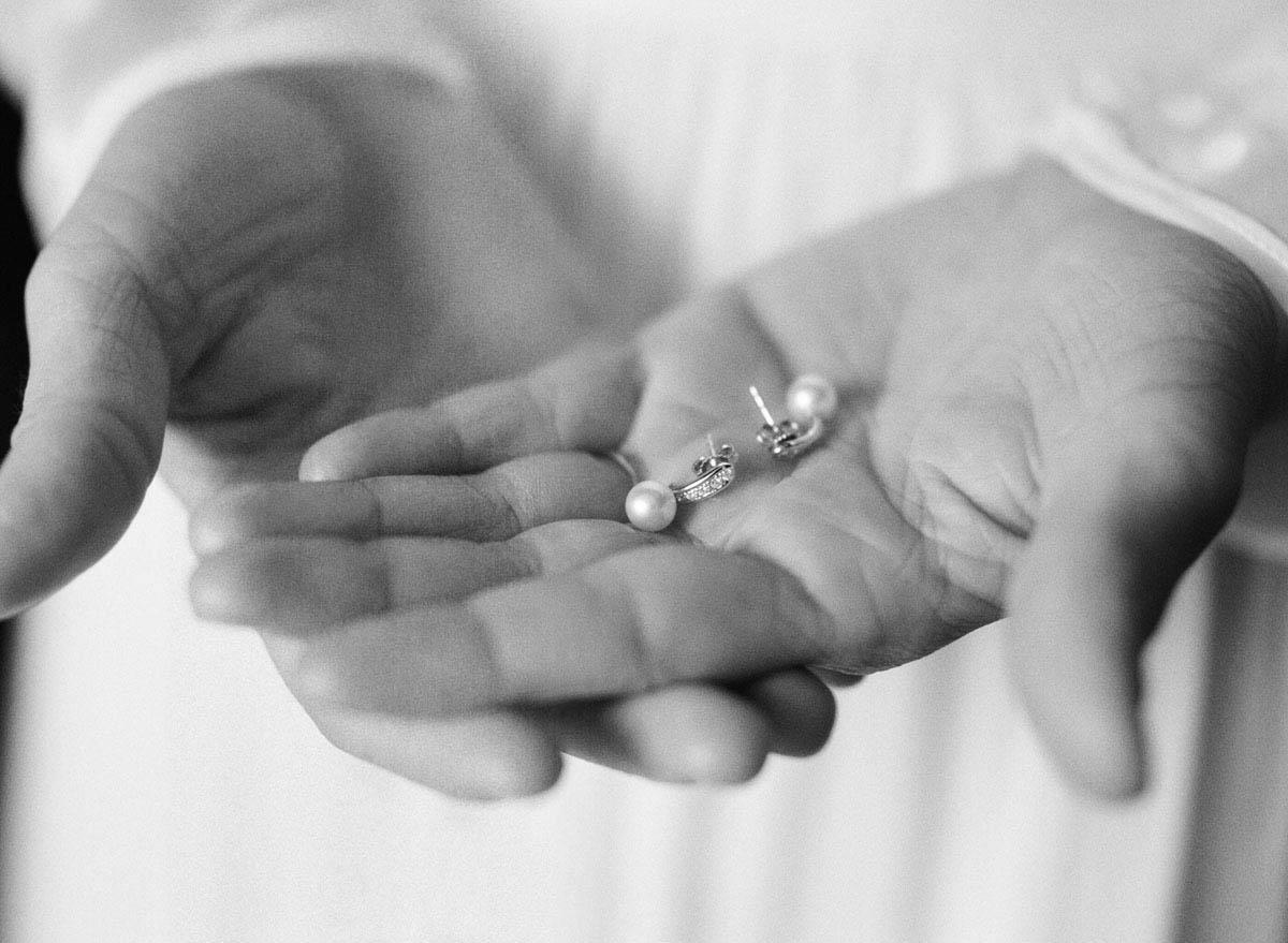 11-bride-holds-earrings-hands.jpg