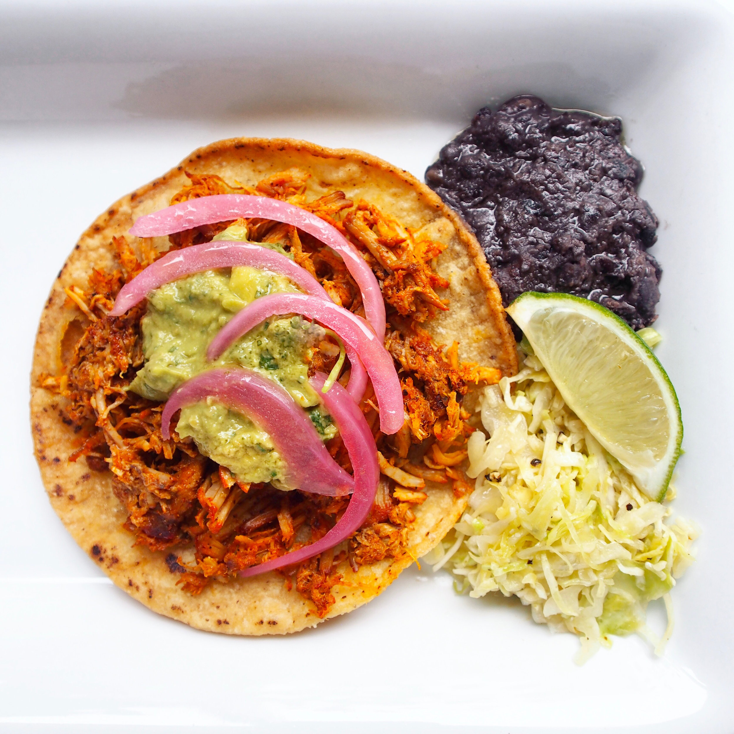 A cochinita pibil taco is served with barbecued pork, avocado salsa, and pickled red onions. Served on the side with cabbage slaw and refried beans! An easy taco recipe, but takes some time.