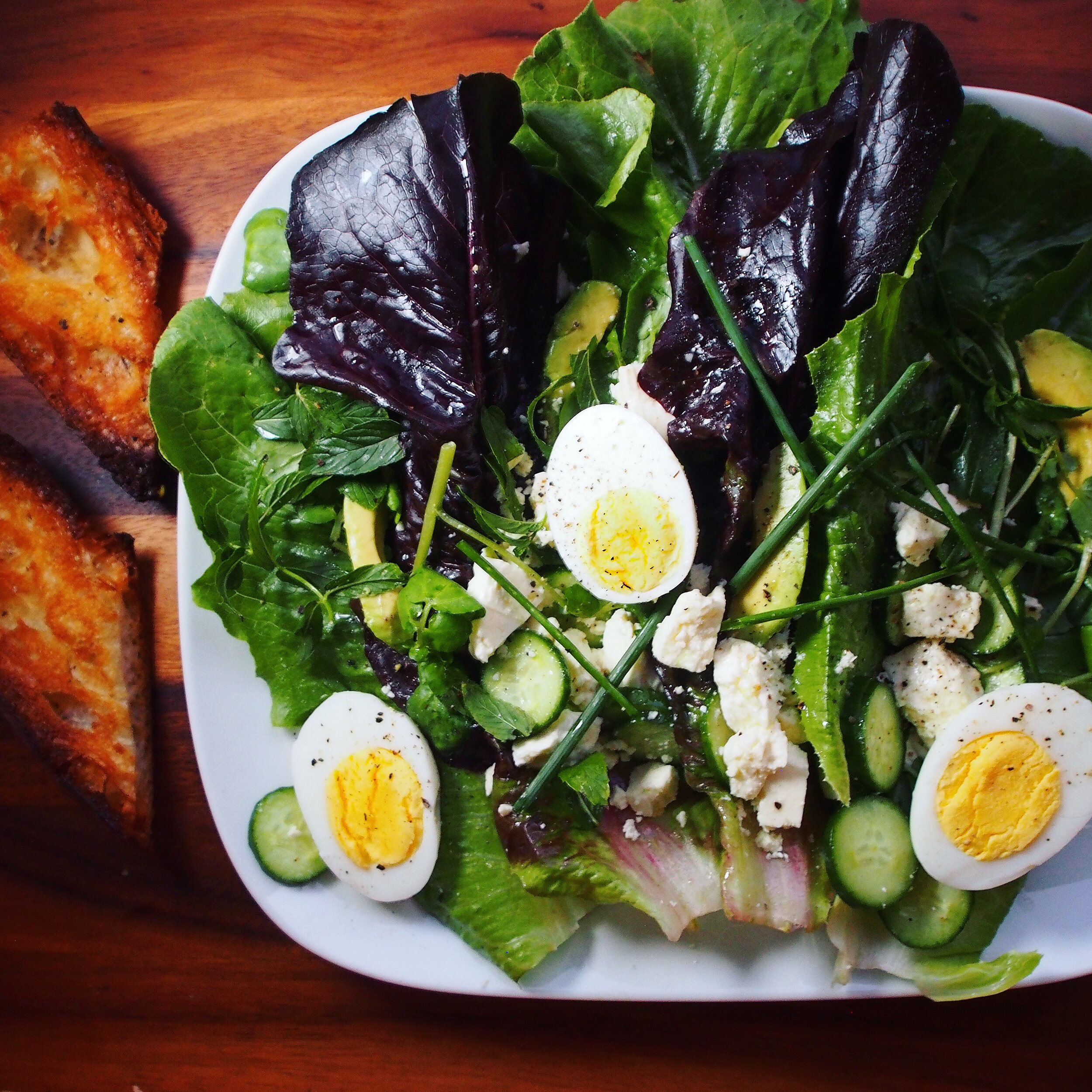 This breakfast salad has eggs, feta, cucumbers, chives, and avocado. It's served with a crunchy toasted baguette. Breakfast salads are the new avocado toast - salad can be eaten any time of the day!