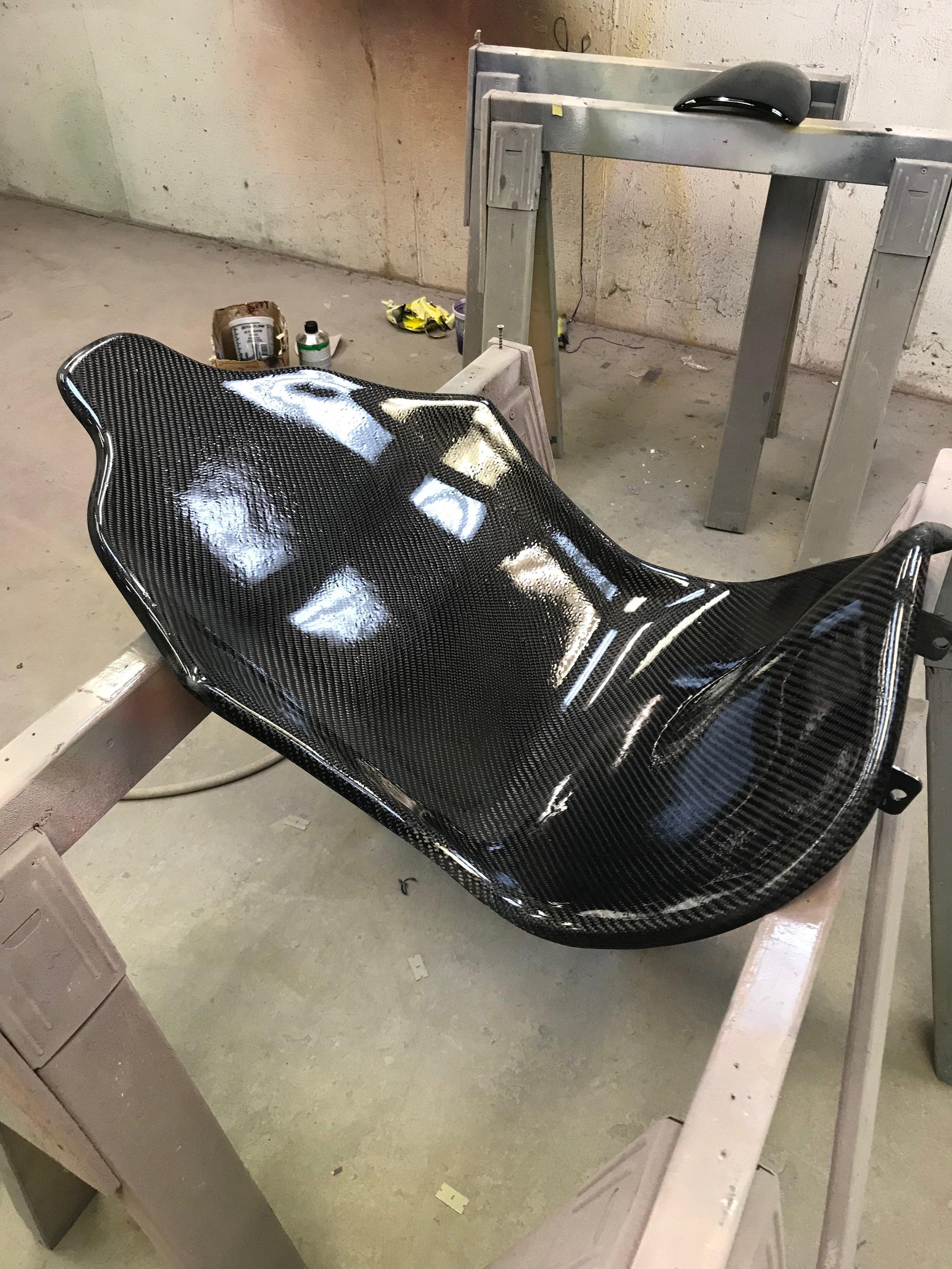 Black Glass - a lightweight carbon fiber + fiberglass racing seat unibody seat, encapsulating all mounting into carbon fiber