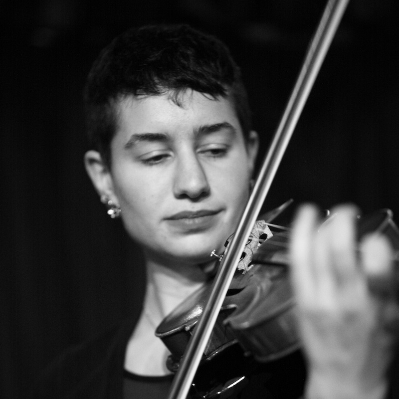 """Zoë Aqua is a violinist based in Brooklyn, NY. In 2017, she served as the full-time understudy for the Klezmatics' Lisa Gutkin in the Broadway production of """"Indecent"""". Quickly becoming an in-demand violinist in the klezmer scene, Zoë is a co-founder of  Tsibele , a five-woman ensemble. Tsibele released their debut album """"It's Dark Outside/ In Droysn iz Finster"""" in September 2017. She also performs regularly with klezmer groups Farnakht, Litvakus, Ternovka, and the Honorable Mentschn. Known for her versatility, she can be seen playing such diverse styles as French-infused reggae with the Blue Dahlia to Mexican folkloric music with the Calpulli Mexican Dance Company. She is a frequent collaborator with Bessie Award-winning choreographer Joya Powell, composing and performing music for two pieces with Powell and the Movement of the People Dance Company, as well as a new work-in-progress to be premiered May 2018."""