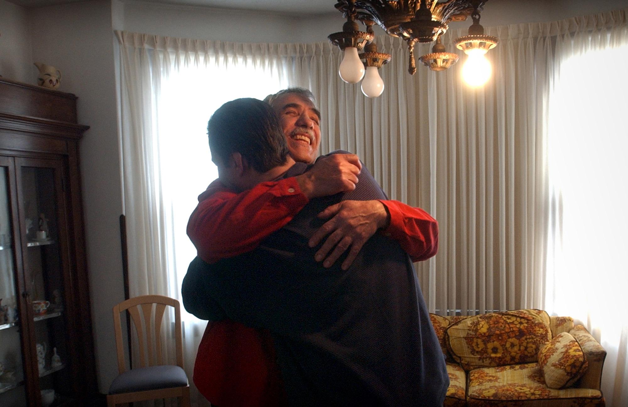 Christos Melacrinos embraces once-homeless Richard Sesek in Sesek's new apartment.