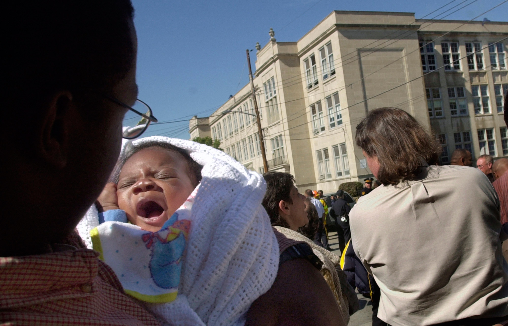 Jamar Foulks holds his seven-week-old son Jamar Jr., who was waking from a nap outside Westinghouse High School.