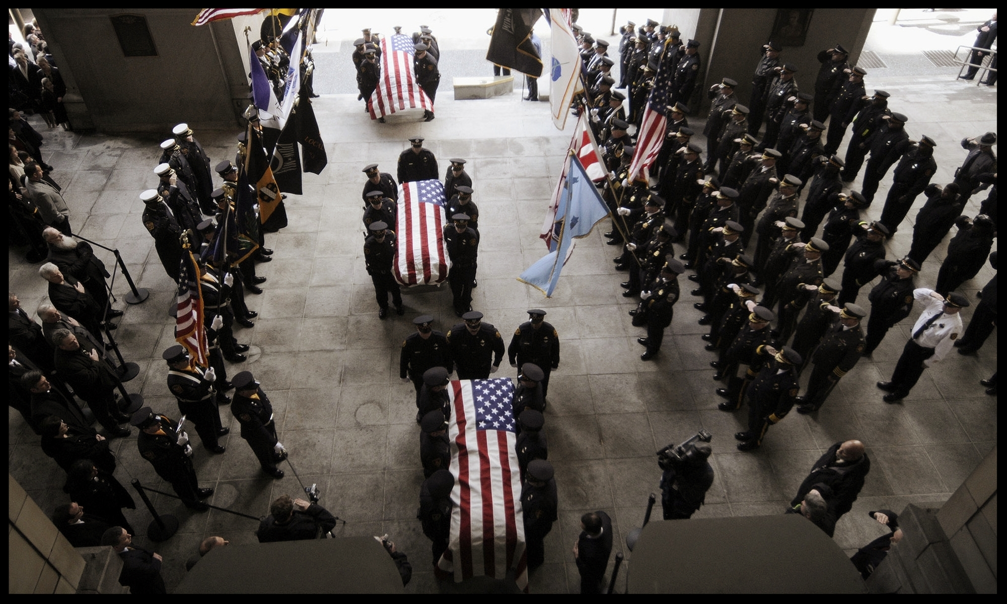 Caskets bearing the bodies of three slain Pittsburgh Police officers are carried into the Pittsburgh City-County Building for public mourning. Click the image to see more photographs.