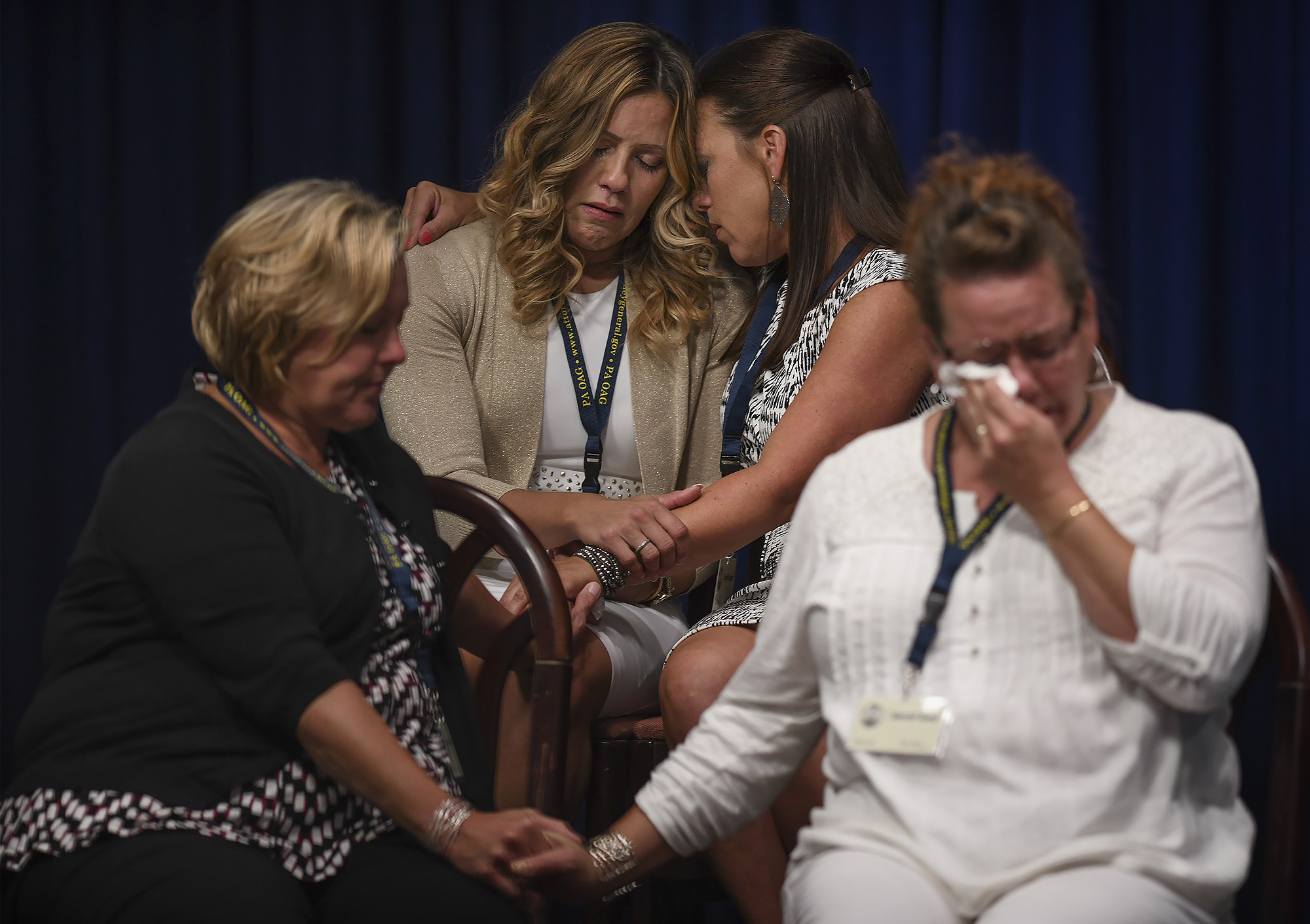 Victims of clergy sexual abuse comfort each other during a press conference detailing seven decades of abuse and cover-up in Pennsylvania.