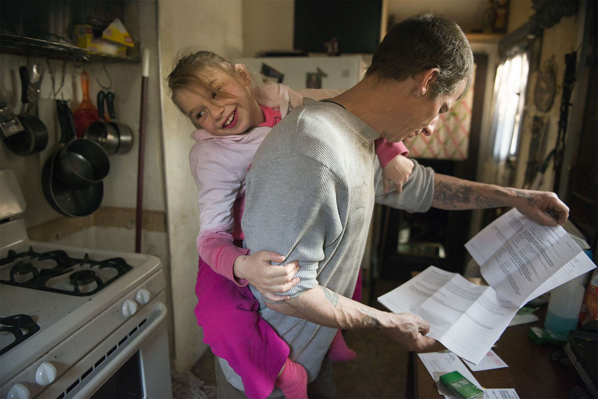 Glenn Jeffries reads a notice to appear in family court while daughter Cathy climbs on his back. Jeffries battles heroin addiction.