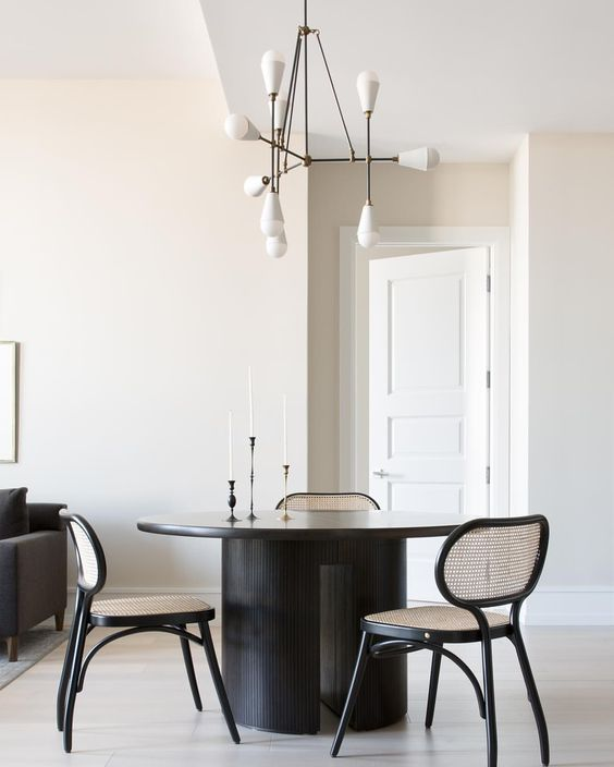 Modern Black Dining Table with Simple Cane Back Chairs with a Transitional Chandelier