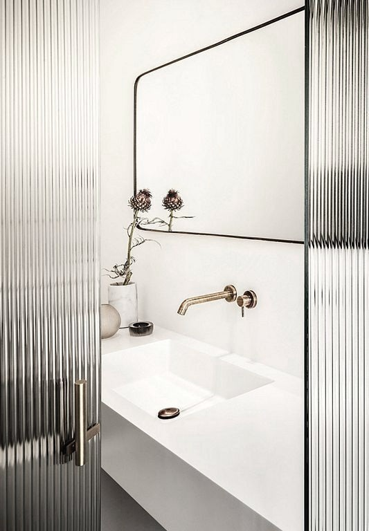 Fluted glass doors leading into a modern white bathroom with a brass wall mounted faucet.jpg