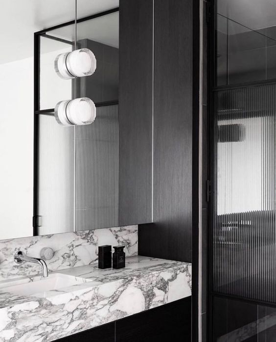 Fluted Ribbed Glass Shower Doors with Marble Slab Sink and wall mounted faucet.jpg