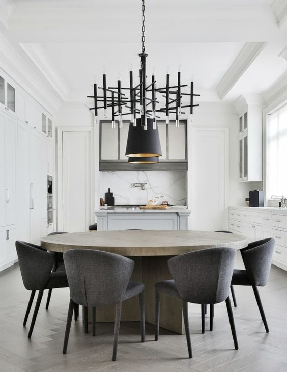 bleached round oak dining table with grey dining chairs with a black geometric Modern chandelier.jpg