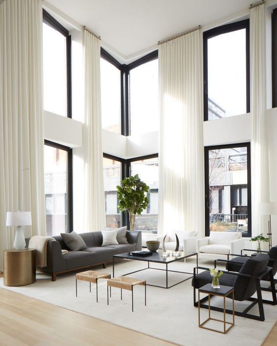 Large open living room space with tall windows floor to ceiling and huge white and cream area rug.jpg