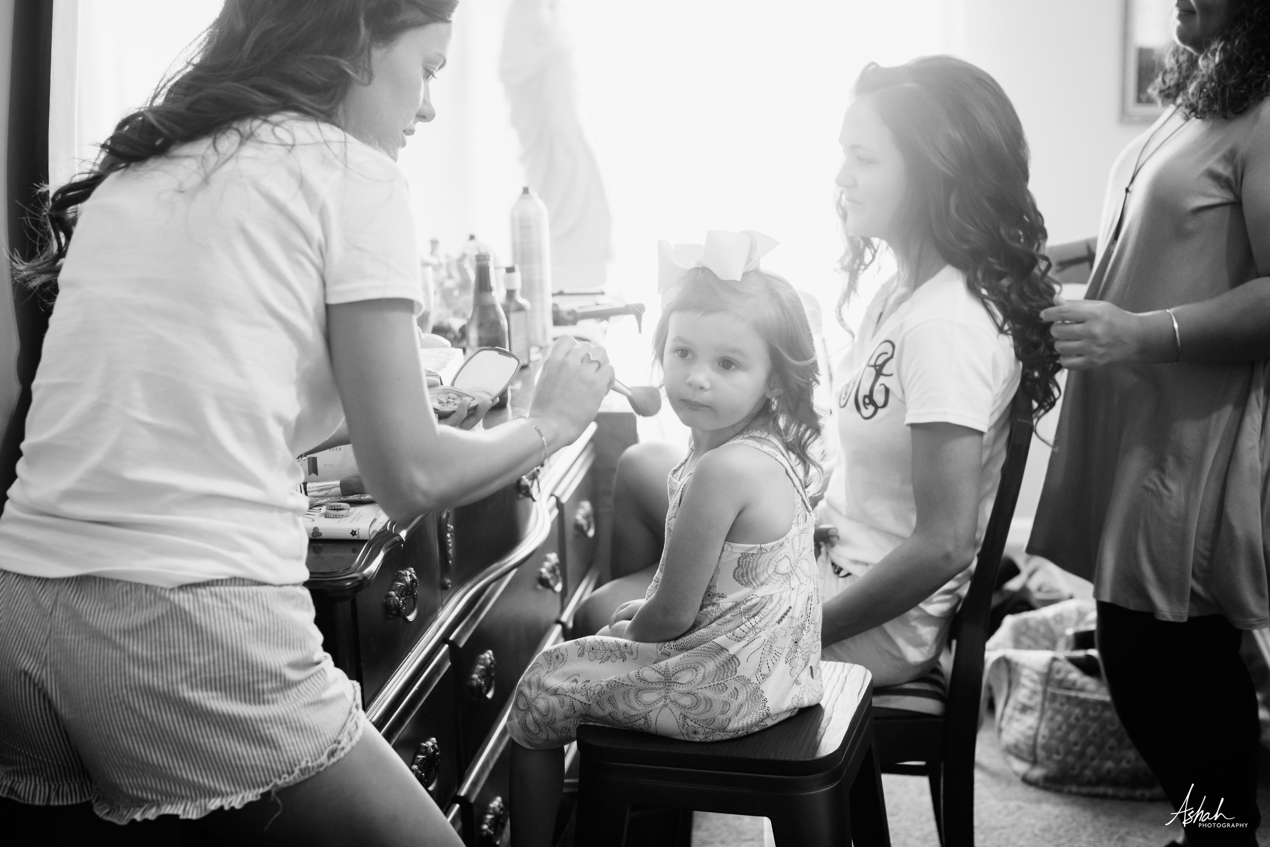 Precious flower girl getting pampered next to the bride | Photo:  Ashah Photography