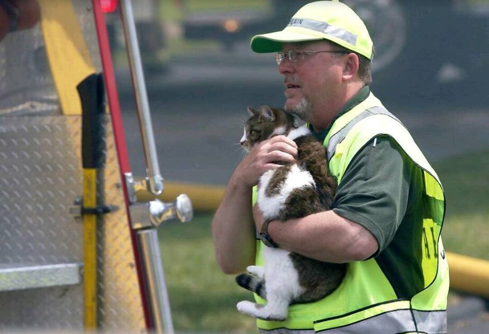On May 24 2015, East Side Fire responded to a fire in a 16-unit apartment complex. Pictured is Chaplain Coons safeguarding a pet rescued from the fire. Photo credit Belleville News Democrat