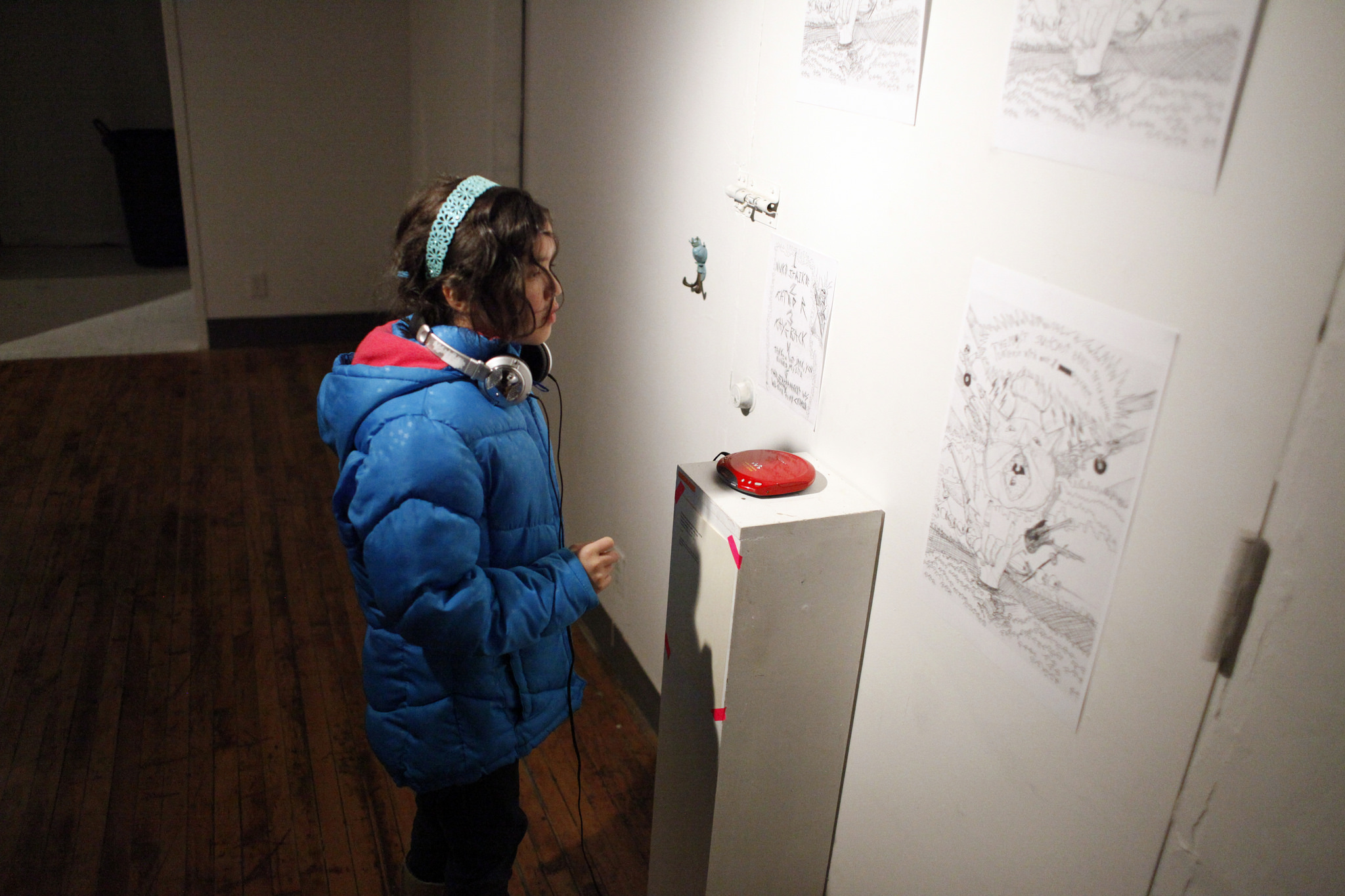 """Young person listens to the music of a rock band made up of 11 year olds at the """"Treats"""" exhibition, a collaboration between artist Rachel Harper and 11-year old Ada Grey. Rachel's """"Seen + Heard"""" project was supported by CAD's """"Learning Is A Lifestyle"""" project."""