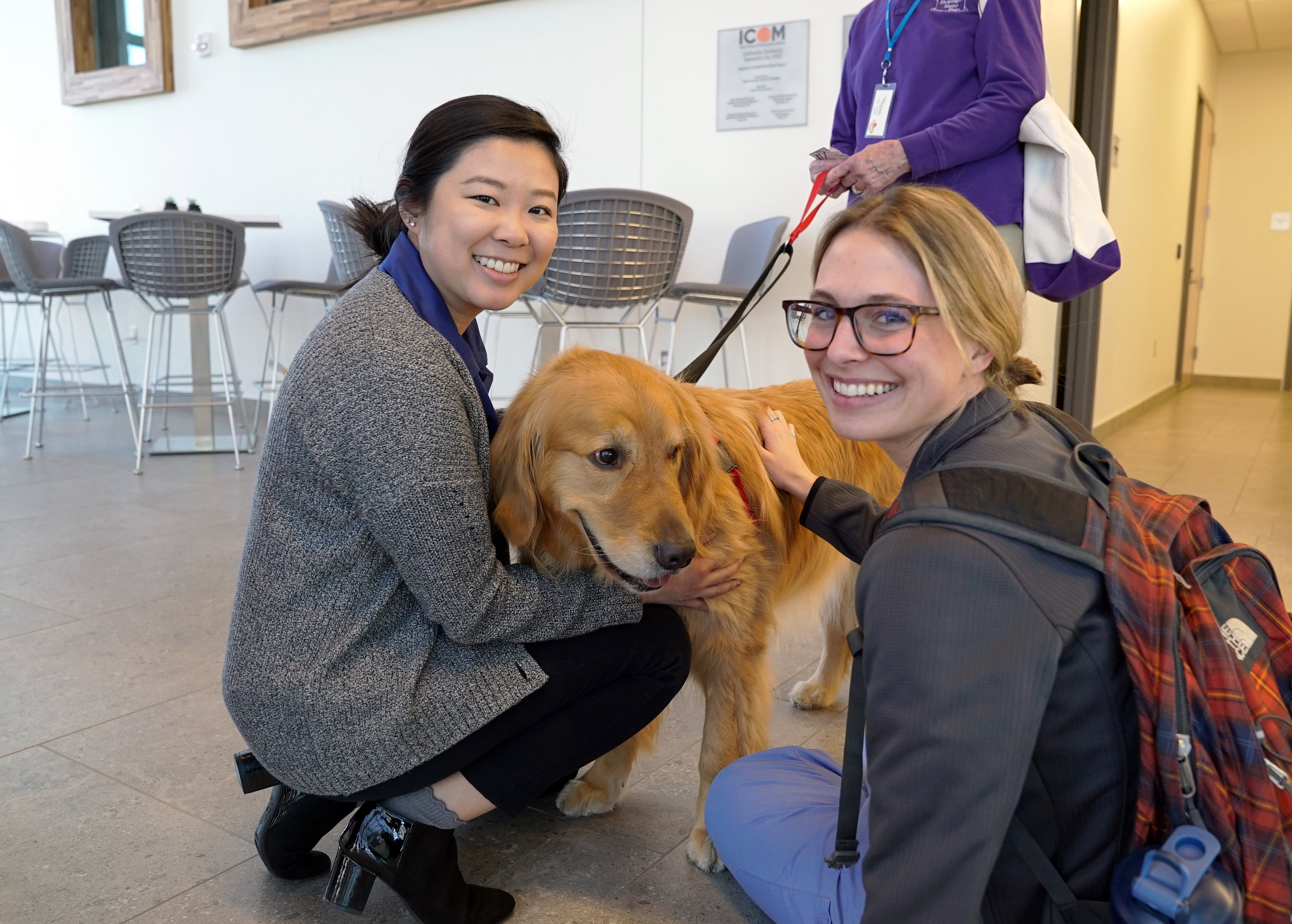Kimberly Lam, OMS-I, and Sophia Robinson, OMS-I, pet Blaze, a therapy dog.