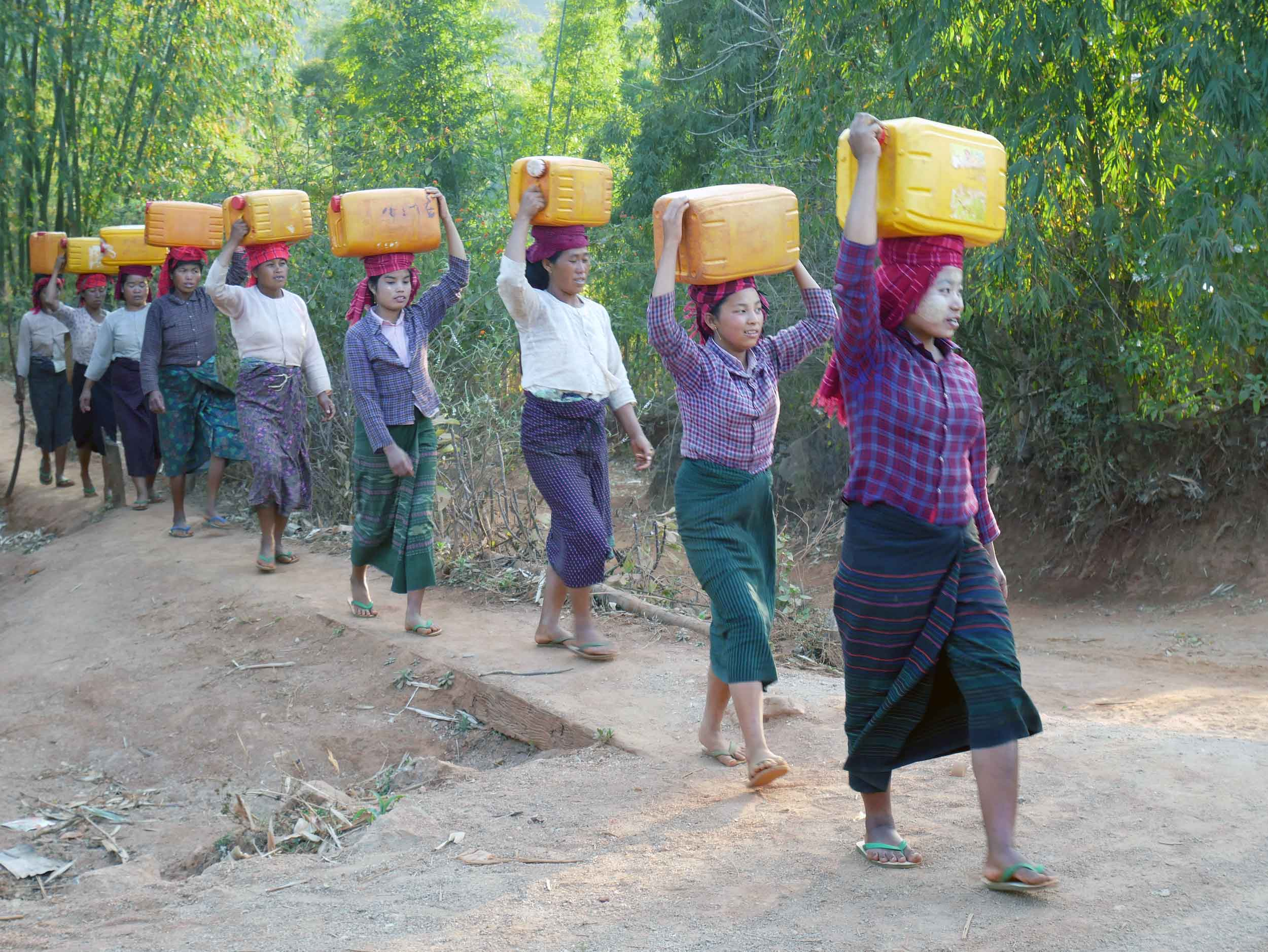 After a rest, we departed the village for a short hike to watch sunset, and en route, we passed the local women returning with water (Feb 20).