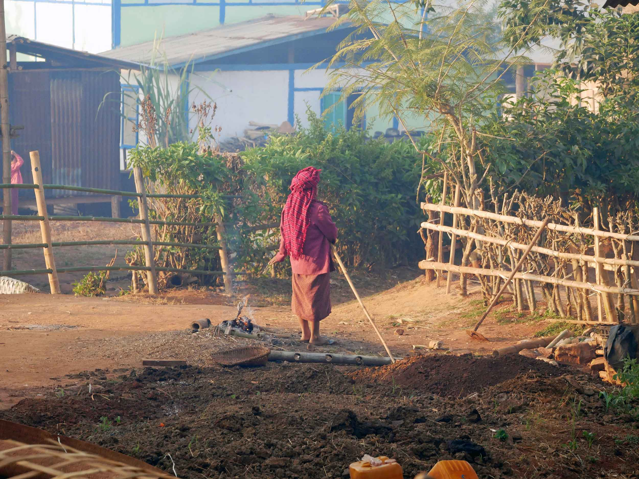Morning life in the village as a women prepares a small fire for warmth (Feb 21).